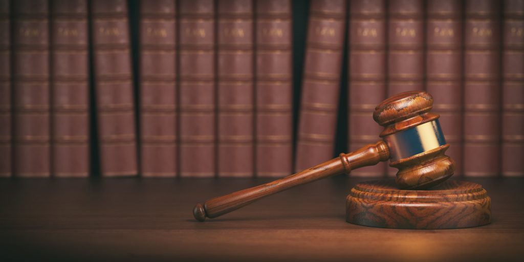 Gavel on the background of vintage lawyer books. Concept of law