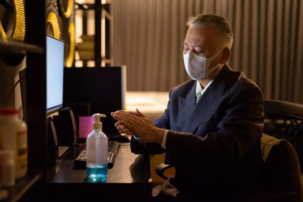 Mature Japanese businessman with mask using hand sanitizer while working overtime at home late at